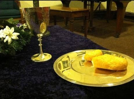 Silver Communion chalice and plate with bread. There is an articifial flower to the left of the chalice, and it all sits on a dark velvet cloth.