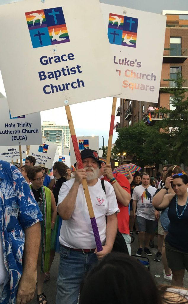 """A white man with a white beard, a friendly smile, white Grace Baptist Church T-shirt, jeans, and a black hat holds a sign that says """"Grace Baptist Church"""" in a crowd of people at a Pride Parade."""